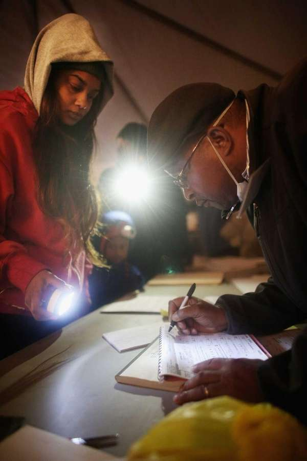Rockaway resident Sheresa Walker, left, uses a flashlight