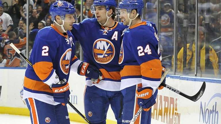 John Tavares, center, celebrates with teammates Mark Streit,