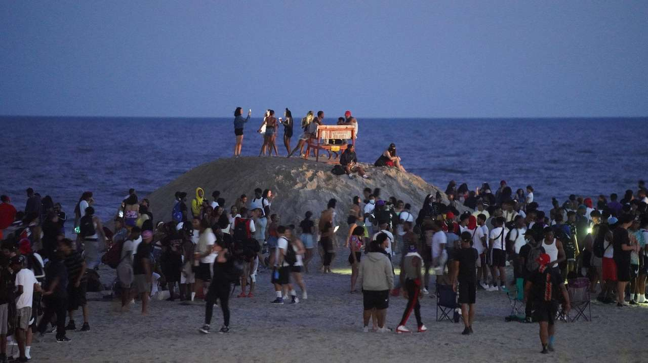 A young people congregate on the beach in
