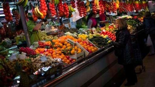 A woman buys fruit at a market in