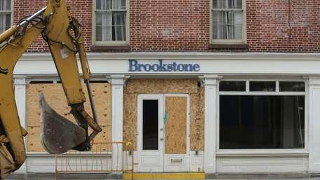 A backhoe is driven past the shuttered Brookstone