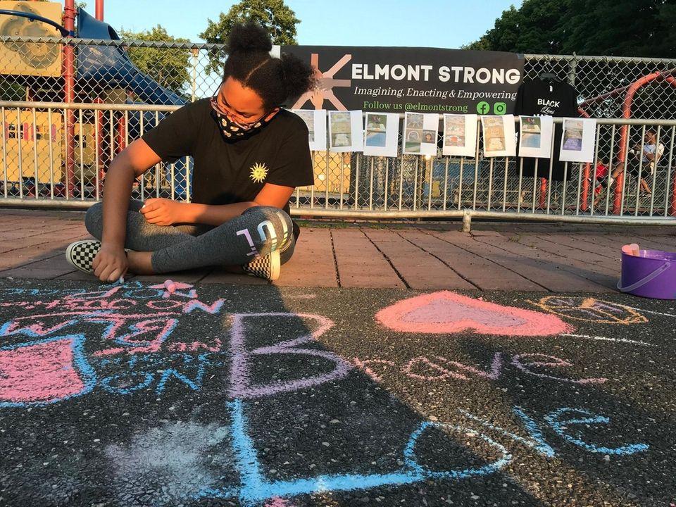 Atira Hall, 12, draws on the sidewalk at