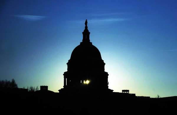 The Capitol Dome silhouetted against the rising sun