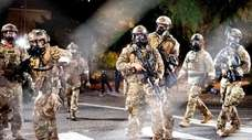 Federal agents in camo and tactical gear disperse