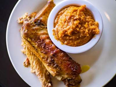 A fried turkey wing with sweet potato pudding