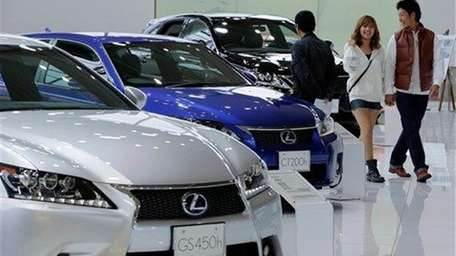 A couple walk by Lexus models displayed at
