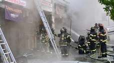 Firefighters battle a blaze in a row of