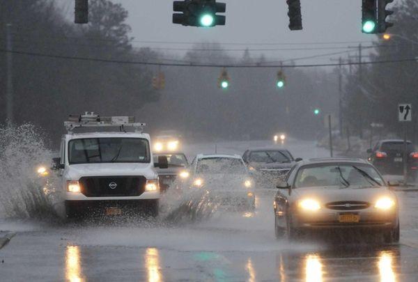 Vehicles splash through flooded Horseblock Road, just west