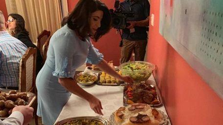 Sen. Anna Kaplan sets plates on a table