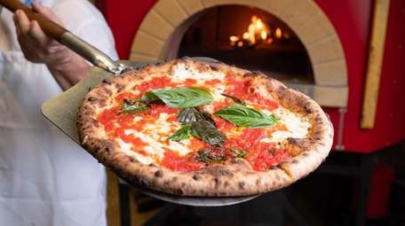 Pizzaiolo Jerry Miele holds a Margherita pizza in