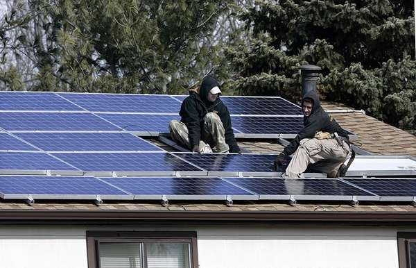 James Stritzki and Alex Morez, right, install solar