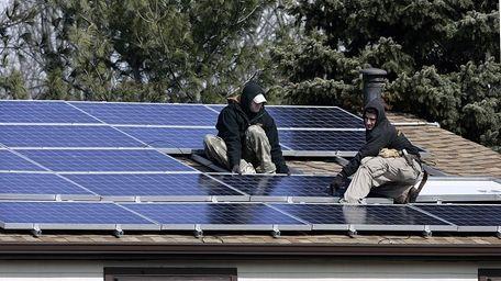 James Stritzki and Alex Morez, right, install solar