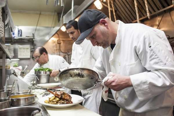 Chef Michael Baratto plates an entree in the