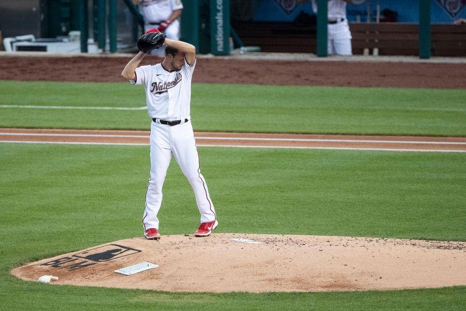 Washington Nationals starting pitcher Max Scherzer wipes his