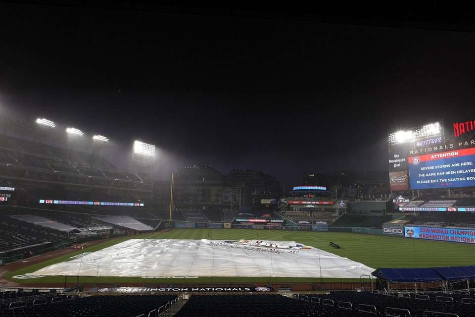 Washington Nationals grounds crew covers the infield with