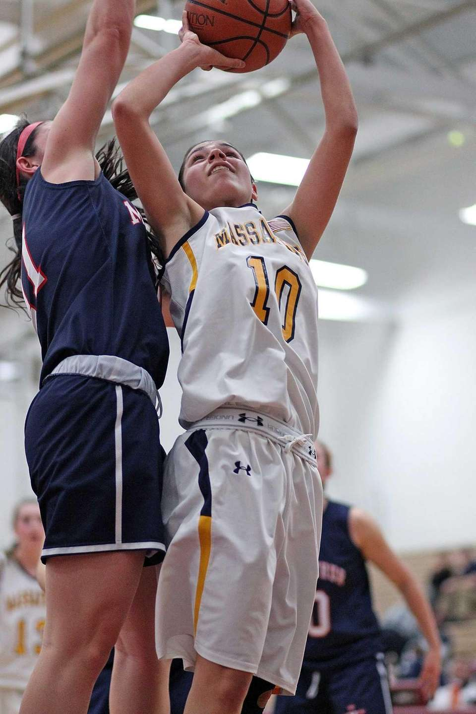 Massapequa's Olivia Batista shoots from under the boards