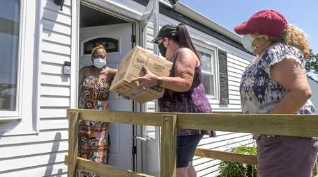 Volunteer Marie Galeazzi delivers a box of home-cooked