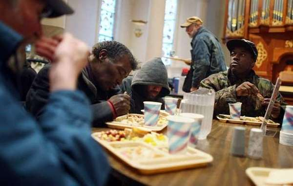 Visitors eat free lunch at a soup kitchen