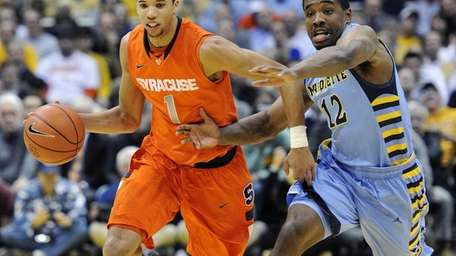 Syracuse's Michael Carter-Williams (1) dribbles past Marquette's Derrick