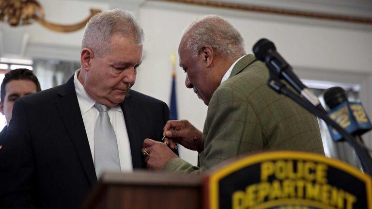 Mount Vernon Mayor Ernie Davis pins the shield