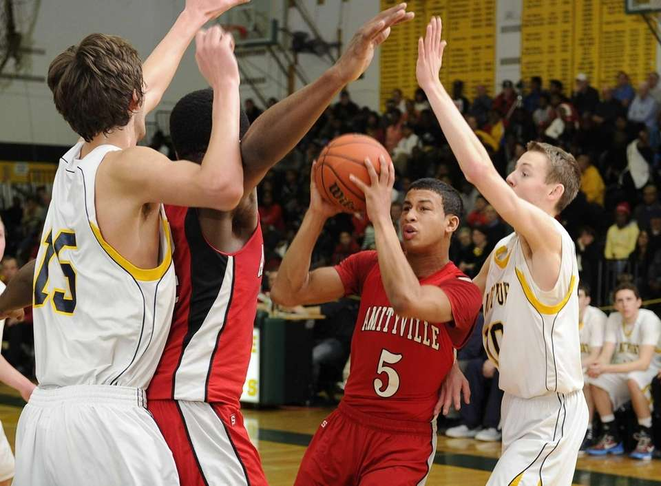 Amityville's Mike Smith is pressured by Northport defenders
