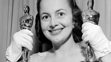 Olivia de Havilland holds two Oscars as she