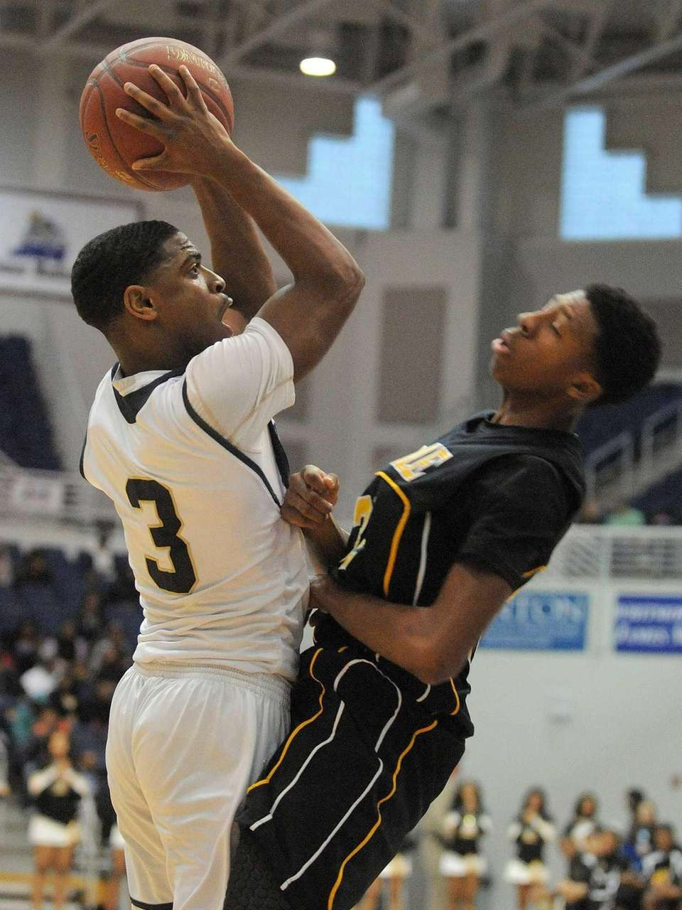 Baldwin's Travais Hylton, left, looks to drive past