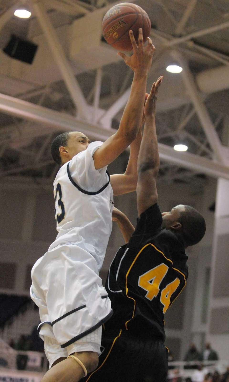 Baldwin's Eric Mack, left, looks to shoot over