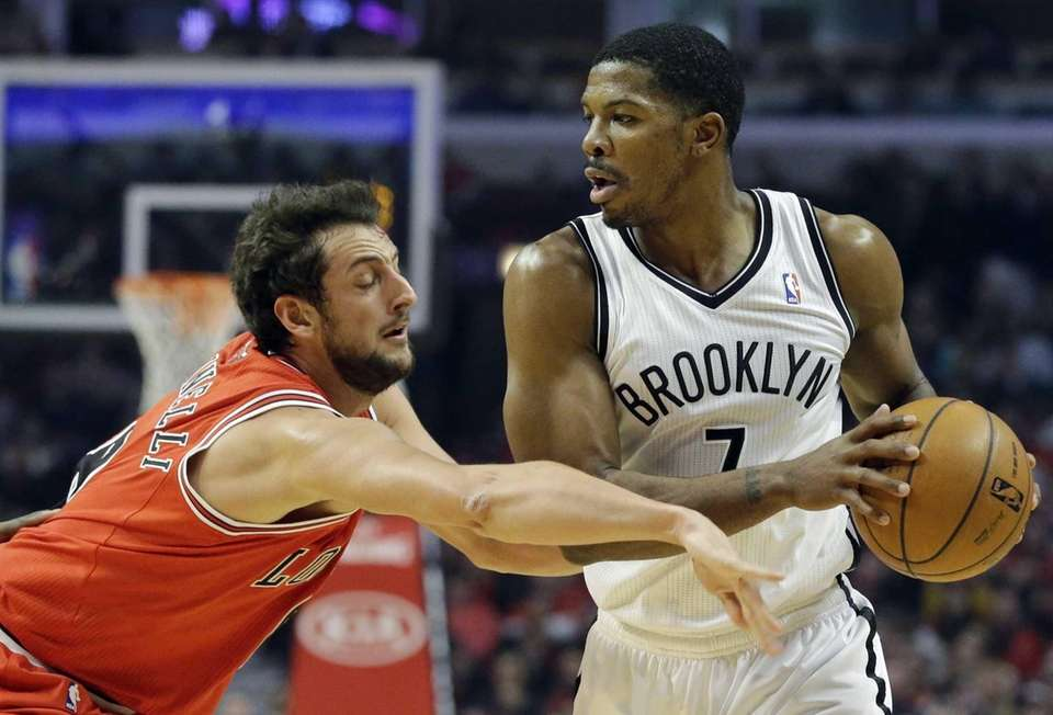 Nets guard Joe Johnson, right, looks to pass