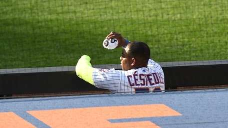 Mets DH Yoenis Cespedes watches from the dugout