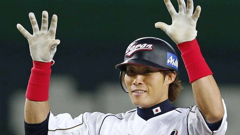 Japan's rightfielder Yoshio Itoi reacts after hitting an