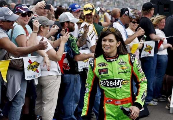 Danica Patrick smiles as she walks past fans