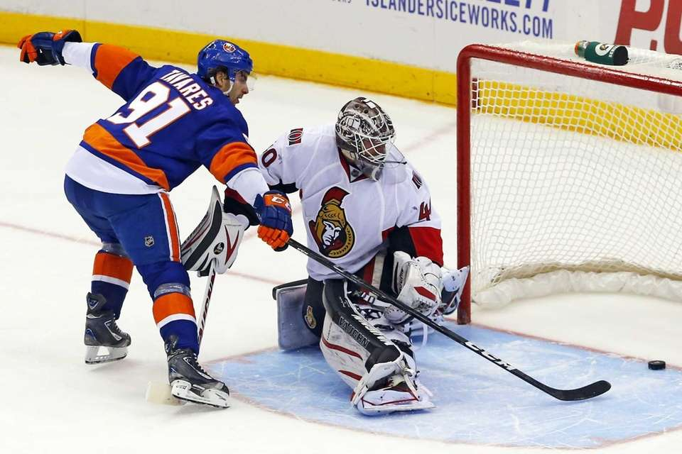 John Tavares slips the puck behind Ottawa Senators