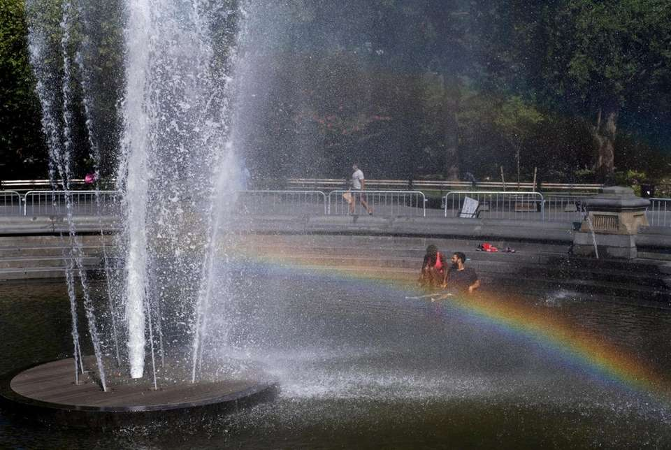 People stay cool as a rainbow forms in