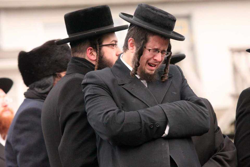 Mourners gather outside the Satmar synagogue during funeral