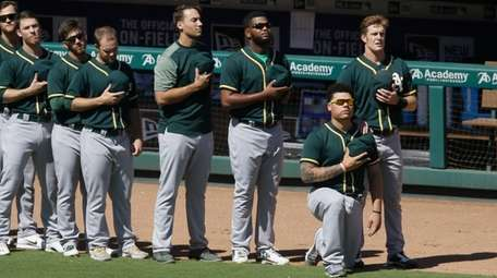 Oakland Athletics catcher Bruce Maxwell takes a knee