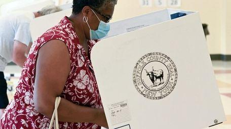 A voter casts a ballot at Aquebogue Elementary