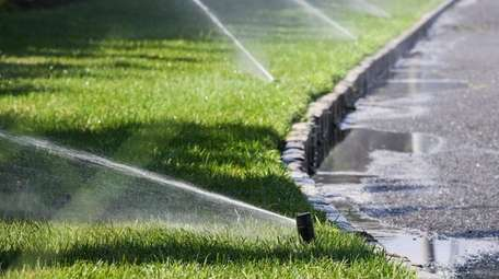 Water sprinklers run outside a home in Sayville,