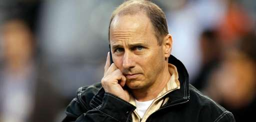 Yankees general manager Brian Cashman talks on the