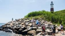 People walk along the shoreline next to the