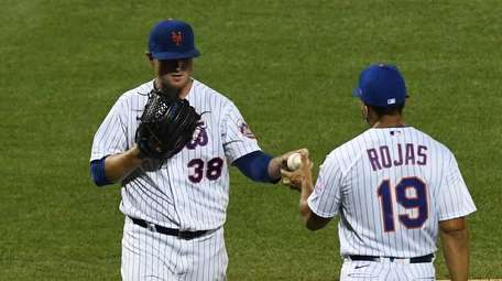 Mets manager Luis Rojas takes the ball from