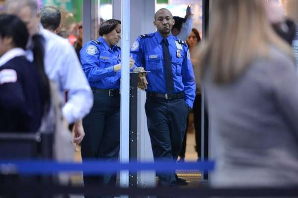 Two TSA agents wait for passengers to go