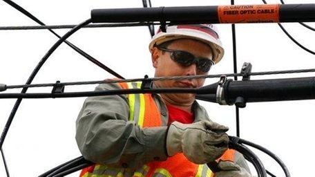 Verizon lineman Clemente Calma installs fiber optic cable