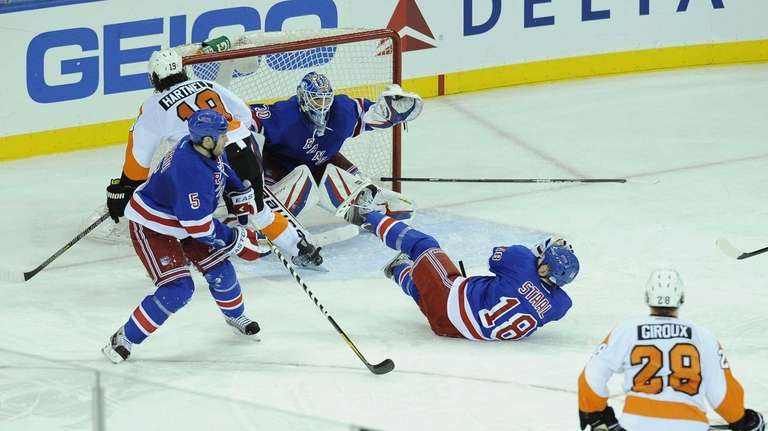 Marc Staal of the Rangers gets hit by