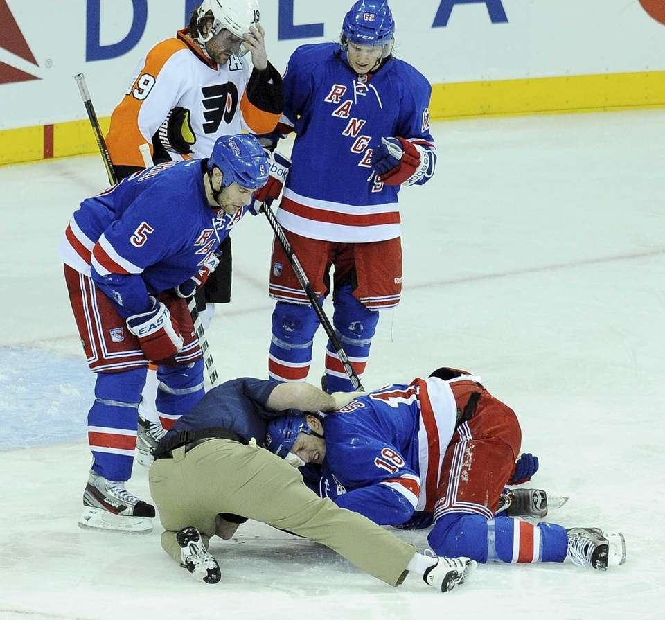 Marc Staal of the Rangers is assisted by
