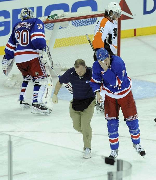 Marc Staal is assisted off the ice after