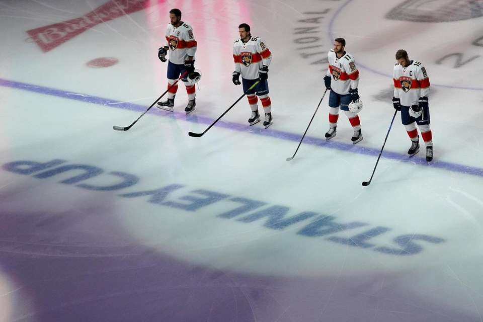 The Florida Panthers stand on the ice during