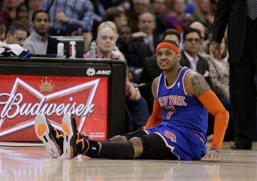 Carmelo Anthony sits up after falling during the