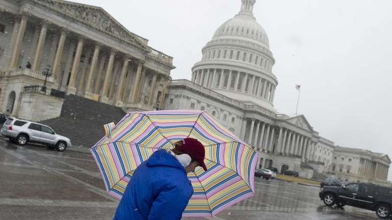A woman walks past the US Capitol in