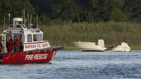 Wantagh Fire Department personnel work near damaged boat